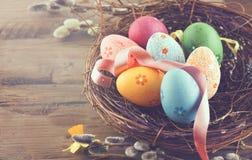 Fundo de Easter Os ovos coloridos bonitos no ninho com mola florescem sobre a madeira Fotos de Stock