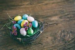 Fundo de Easter Os ovos coloridos brilhantes no ninho com mola florescem sobre o fundo escuro de madeira Foco seletivo com Foto de Stock Royalty Free