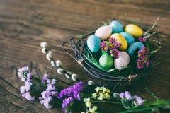 Fundo de Easter Os ovos coloridos brilhantes no ninho com mola florescem sobre o fundo escuro de madeira Foco seletivo com Fotos de Stock Royalty Free