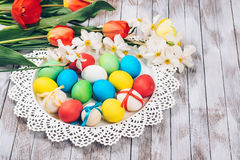 Fundo de Easter Ovos da páscoa e flores coloridos da mola no fundo de madeira branco Imagens de Stock