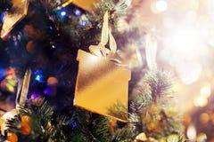 Fundo de incandescência do Natal e do ano novo com decoração do feriado O ouro de luzes de-focalizadas decorou a árvore Fotografia de Stock