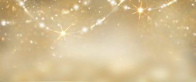 Fundo de incandescência dourado do Natal Contexto defocused do brilho do sumário do feriado com alcatrões e festões piscar fotos de stock royalty free