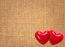 Fundo de linho da textura com dois corações vermelhos Fotografia de Stock