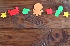 Fundo de madeira com os animais de mar de papel coloridos Fotos de Stock