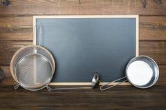 Fundo de madeira com um quadro e os utensílios de cozimento imagens de stock