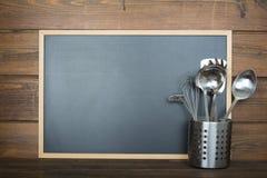 Fundo de madeira com um quadro e os utensílios de cozimento imagem de stock