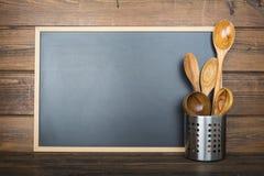 Fundo de madeira com um quadro e os utensílios de cozimento fotos de stock