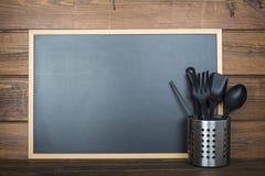 Fundo de madeira com um quadro e os utensílios de cozimento imagens de stock royalty free