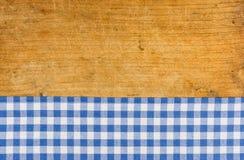 Fundo de madeira com uma toalha de mesa quadriculado azul fotografia de stock royalty free