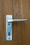 Fundo de madeira da textura da maçaneta de porta europeia de Chrome do metal fotografia de stock