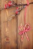 Fundo de madeira do Natal com ramo da baga do azevinho e doces Ca Imagens de Stock