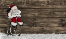 Fundo de madeira do Natal com Santa em uma bicicleta Cumprimento engraçado fotos de stock royalty free