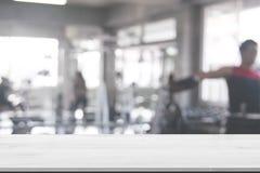 Fundo de madeira do tampo da mesa no fundo borrado do sumário do gym da aptidão de equipamentos do exercício para a composição do foto de stock royalty free