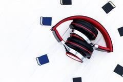 Fundo de madeira no estilo antigo Acessórios musicais os fones de ouvido são vermelhos Cartão de memória tenha a tonificação Espa fotografia de stock
