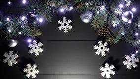 Fundo de madeira preto do Natal Arranjado com ramos do pinho na parte superior, com luzes, brinquedos do ano novo filme