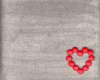 Fundo de madeira rústico com o coração vermelho brilhante feito fora do candi Imagens de Stock Royalty Free