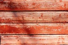 Fundo de madeira velho pintado com pintura vermelha com uma textura das quebras e dos riscos foto de stock
