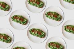 Fundo de muitos brindes ou sanduíches deliciosos e nutritivos do vegetariano com abacate e guacamole em um mínimo Imagens de Stock Royalty Free