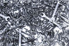 Fundo de muitos rebites, wrenchs, parafusos e parafusos diferentes do metal da cor de prata e preta foto de stock royalty free