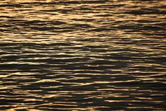 Fundo de ondas do mar e da luz solar dourada da cor foto de stock