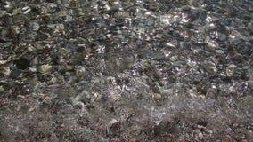 Fundo de ondas transparentes do mar corrido sobre no Pebble Beach bonito vídeos de arquivo