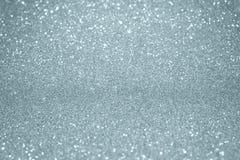 Fundo de prata da textura do brilho com efeito da luz do borrão e partículas efervescentes brilhantes Brilho luz de prata ou bril foto de stock