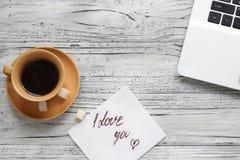 Fundo de um Valentim em uma tabela de madeira com um copo do portátil de Imagens de Stock