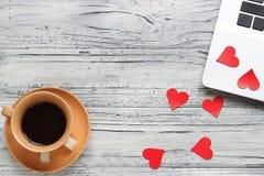 Fundo de um Valentim em uma tabela de madeira com um copo do portátil de Imagem de Stock