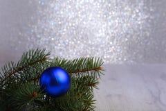 Fundo decorativo com ramos do abeto e as bolas azuis na prata Conceito do feriado do cartão de Natal fotografia de stock