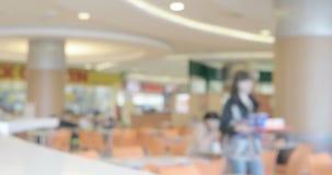 Fundo defocused borrado do salão público da praça da alimentação que mostra o pessoa comendo e de passeio, área do anúncio public filme