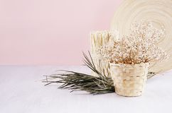 Fundo delicado da baunilha da mola com as flores secas brancas e prato verde do ramo e o de bambu na tabela clara e na parede cor Fotografia de Stock