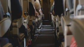 Fundo disparado do corredor claro interior moderno da classe de economia do avião durante o voo com os passageiros em seus assent vídeos de arquivo