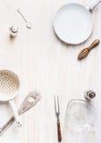Fundo do alimento com a frigideira vazia, cozinhando a colher, o escorredor e as bacias na mesa de cozinha branca Foto de Stock