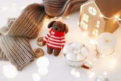 Fundo do ano novo e do Natal com o brinquedo do cachorrinho do cão com uma xícara de café e velas no fundo branco fotos de stock