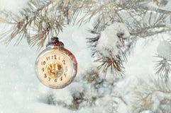 Fundo do ano novo e do Natal em tons do vintage Brinquedo do Natal do ano novo no ramo de árvore nevado do abeto Foto de Stock Royalty Free