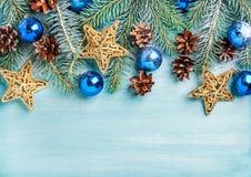 Fundo do ano novo ou do Natal: o abeto ramifica, bolas de vidro azuis, cones, estrelas douradas sobre o contexto de madeira de tu Imagem de Stock