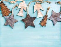 Fundo do ano novo ou do Natal: os anjos de madeira, as estrelas e os abeto pequenos sobre o azul pintaram o contexto, espaço da c Foto de Stock