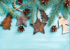 Fundo do ano novo ou do Natal: os anjos de madeira, as estrelas, os abeto pequenos, os cones e os ramos sobre o azul pintaram o c Fotografia de Stock