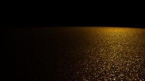 Fundo do brilho - o brilho dourado efervescente em uma fase iluminou-se por um projetor do direito na frente de um fundo preto Fotografia de Stock