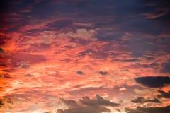 Fundo do céu do por do sol com cores impetuosas das nuvens, as alaranjadas e as azuis imagens de stock