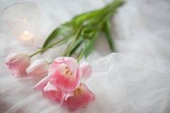 Fundo do casamento de matéria têxtil com tulipas e vela cor-de-rosa Dia do ` s da mulher imagens de stock royalty free