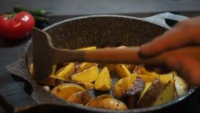 Fundo do cozimento home Alimento gordo Batatas unpeeled amarelas rústicas apetitosas cozinhadas com o azeite fritado em uma bande vídeos de arquivo