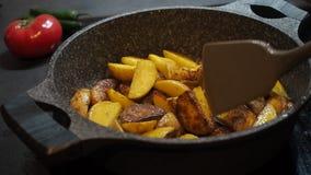 Fundo do cozimento home Alimento gordo Batatas unpeeled amarelas r?sticas apetitosas cozinhadas com o azeite fritado em uma bande filme