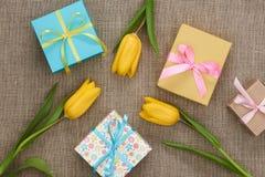 Fundo do dia de mães Tulipas, presentes no pano de saco Foto de Stock