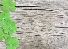 Fundo do dia de St Patrick com os trevos verdes na textura de madeira fotos de stock
