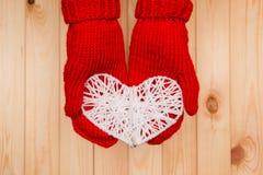 Fundo do dia de Valentim As posses da menina fizeram malha o coração no mitte vermelho Fotografia de Stock