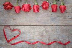 Fundo do dia de Valentim com rosa do vermelho e fita em de madeira imagem de stock