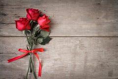 Fundo do dia de Valentim com rosa do vermelho e fita em de madeira Tom de Accounting imagem de stock