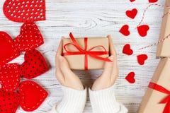 Fundo do dia de Valentim A mão da menina dá a caixa de presente do Valentim com um coração vermelho para dentro em uma tabela de  Imagem de Stock Royalty Free