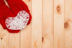 Fundo do dia de Valentim A menina guarda o coração feito malha branco no vermelho Imagem de Stock